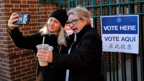 Впервые проголосовавшая девушка делает сэлфи с мамой возле избирательного участка в Нью-Йорке