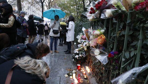 Люди приносят цветы и зажигают свечи у входа в клуб Bataclan в Париже