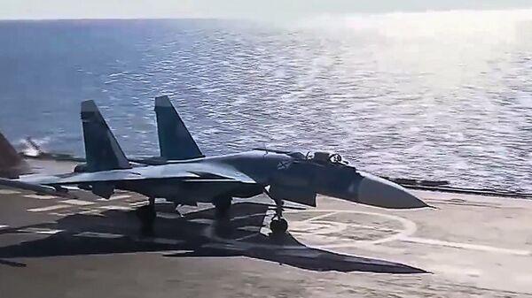 Корабельный истребитель Су-33 ВКС РФ перед взлетом с авианосца Адмирал Кузнецов для нанесения авиаудара по объектам террористов в Сирии. 17 ноября 2016