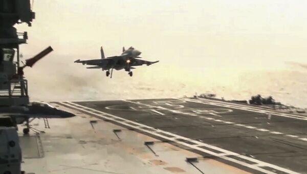 Корабельный истребитель Су-33 ВКС РФ осущестляет посадку на палубу тяжёлого авианесущего крейсера Адмирал Флота Советского Союза Кузнецов после нанесения ракетно-бомбового удара по объектам незаконных вооруженных формирований на территории Сирийской Арабской Республики