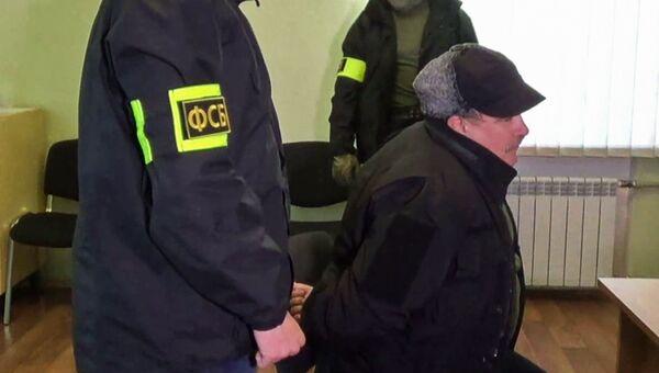 Сотрудники Федеральной службой безопасности РФ конвоируют задержанного по подозрению в государственной измене бывшего военнослужащего штаба Черноморского флота капитан 2 ранга запаса Леонида Пархоменко в Севастополе