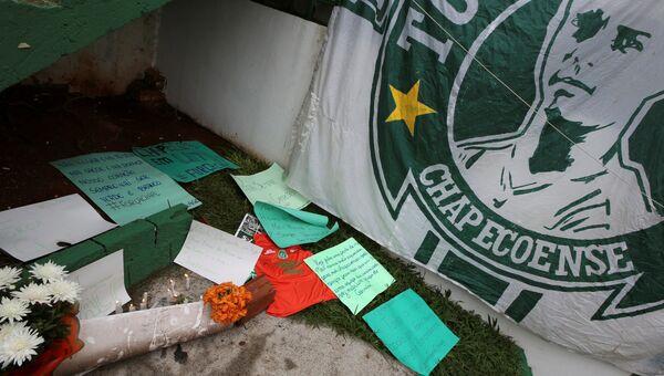 Цветы и флаг футбольного клуба Шапекоэнсе перед стадионом в бразильском городе Шапеко