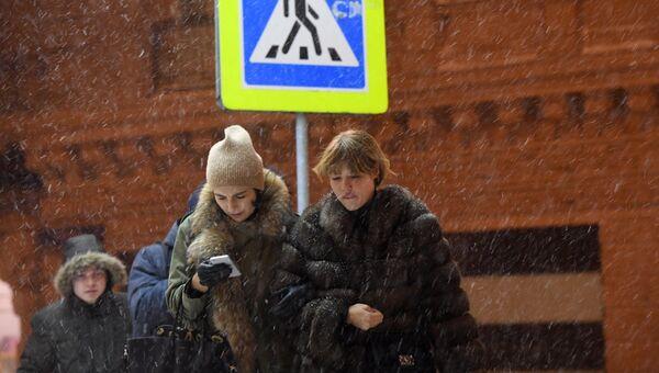 Прохожие в Москве во время снегопада