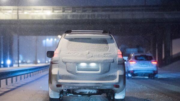 Автомобиль на Ярославском шоссе в Москве во время снегопада