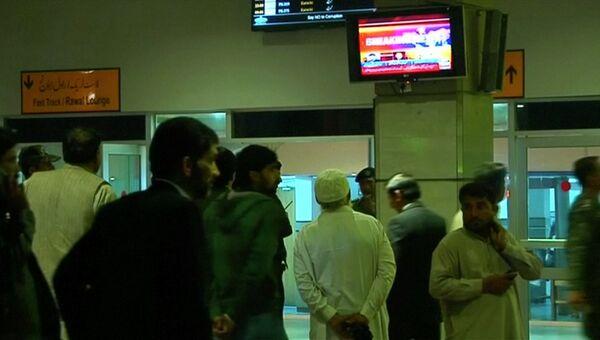 Люди смотрят репортаж об авиакатастрофе самолета авиакомпании PIA в аэропорту Беназир Бхутто в Исламабаде, Пакистан
