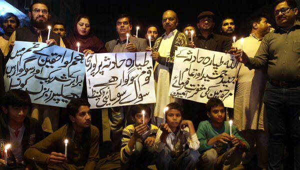 Люди держат свечи в память о жертвах авиакатастрофы самолета авиакомпании PIA в Мултане, Пакистан