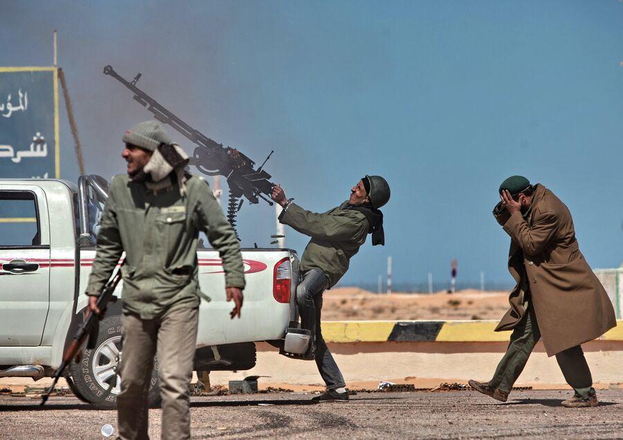 Боец оппозиции стреляет из пулемета в истребитель в городе Рас-эль-Ануф