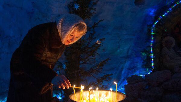 Женщина зажигает свечу в снежном Рождественском вертепе во время праздничной Рождественской службы в Богоявленском соборе в Томске