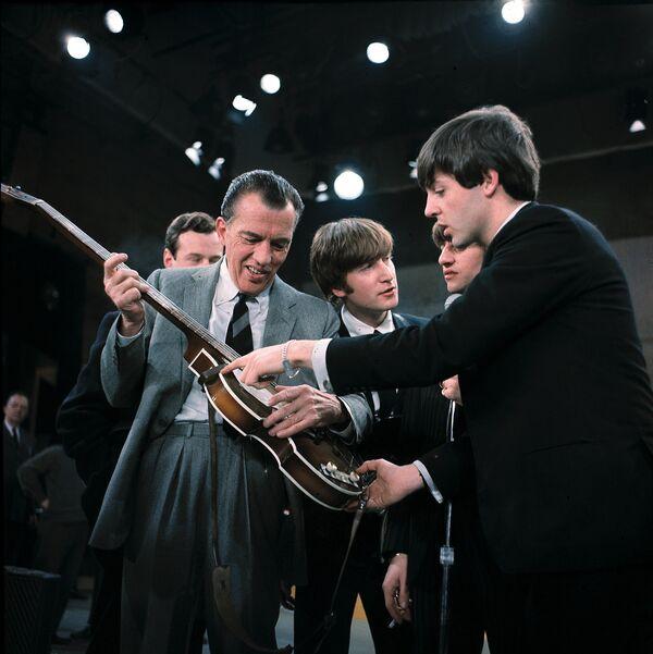 Пол Маккартни показывает свою гитару Брайану Эпстайну