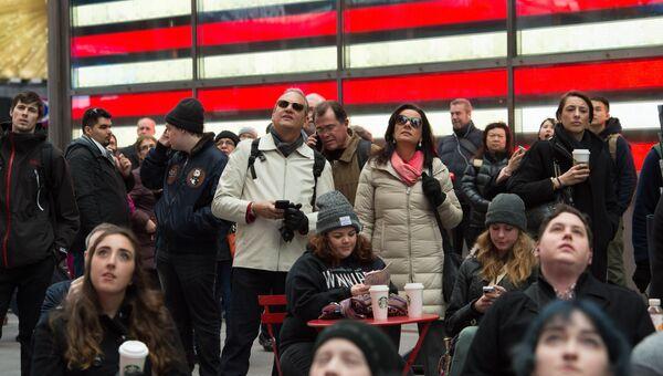 Люди смотрят трансляцию инаугурации Дональда Трампа на Таймс-сквер в Нью-Йорке. 20 января 2017 года