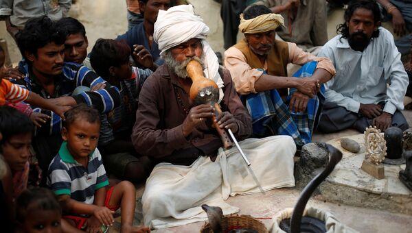 Заклинатель змей играет на флейте перед коброй после утренней молитвы в храме Jogi Dera в штате Уттар-Прадеш, Индия.