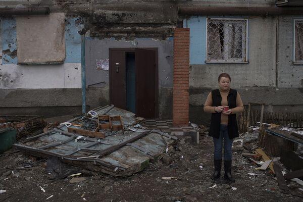 Женщина у входа в поврежденное в результате обстрелов здание в Киевском районе Донецка