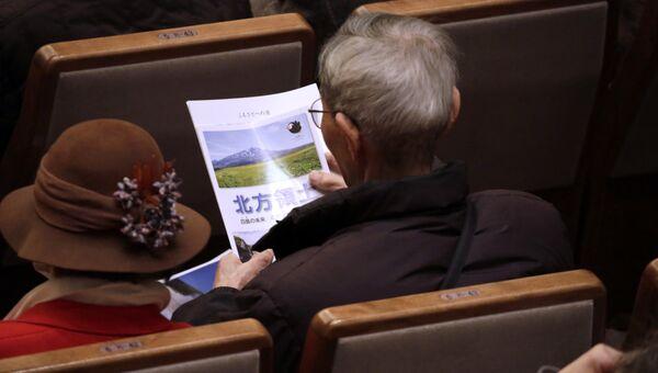 Мужчина читает брошюру Северные территории перед началом мероприятия по случаю Дня северных территорий в Токио