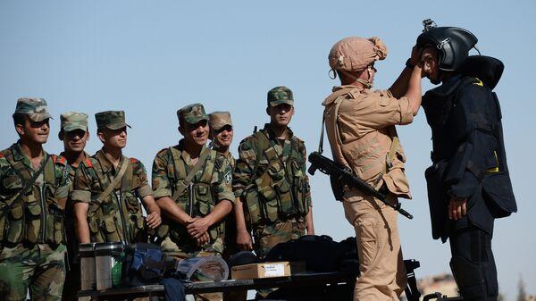 Российский военнослужащий (второй справа) обучает сирийских солдат поисковой тактике и обнаружению взрывных устройств в Пальмире