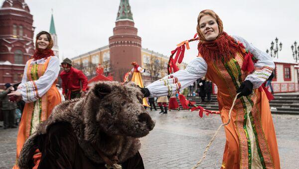 Участницы анимационной программы, одетые в праздничные костюмы, с актером в костюме медведя во время открытия фестиваля Московская масленица на Манежной площади