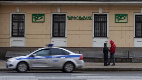 Автомобиль полиции едет мимо здания в Москве, в котором расположен офис Татфондбанка. Архивное фото