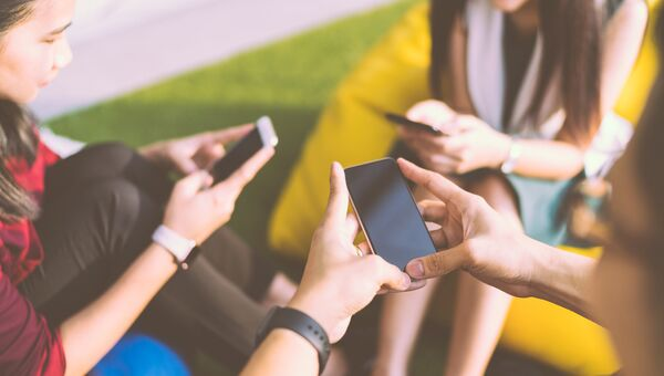 Молодые люди со смартфонами. Архивное фото