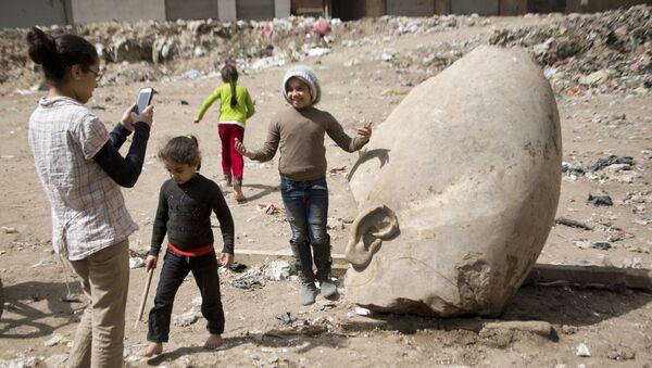 Ребенок фотографируется возле статуи древнеегипетского фараона Рамзеса Второго, обнаруженой археологами в районе Матария в Каире