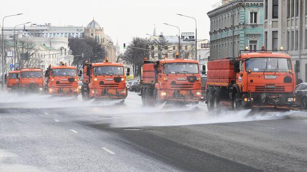 Спецтехника поливает дорогу на улице Новый Арбат в Москве.