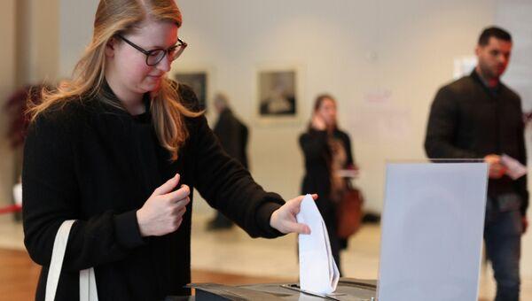 Девушка голосует на избирательном участке в Амстердаме во время парламентских выборов в Нидерландах. Архивное фото
