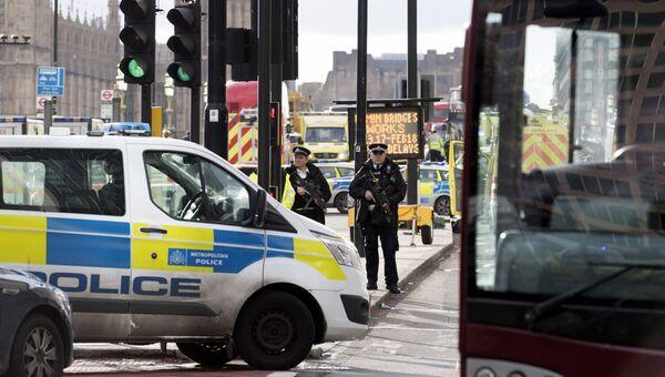 Сотрудники полиции стоят в оцеплении неподалеку от здания британского парламента