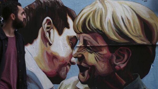 Граффити с изображением премьер-министра Греции Алексиса Ципраса и канцлера Германии Ангелы Меркель на улице в Афинах, Греция