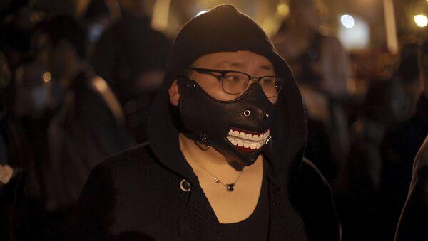 Китайский иммигрант во время акции протеста против убийства французскими полицейскими китайца в Париже