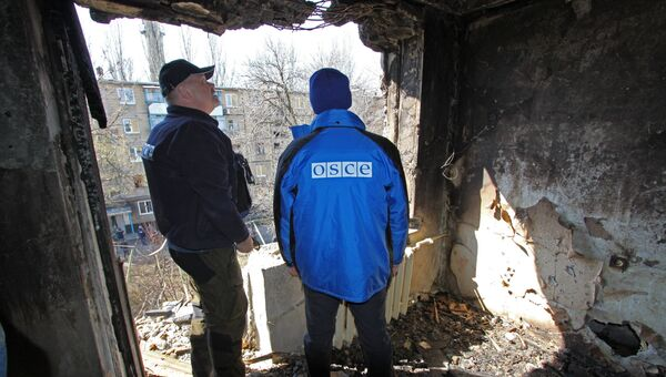Представители ОБСЕ осматривают квартиру жилого дома, поврежденного в результате обстрелов, в Киевском районе Донецка. Март 2017
