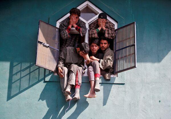 Люди наблюдают из окна мечети за похоронами командира повстанцев, погибшего в бою с индийской армией. Ярипора, Кашмир, Индия