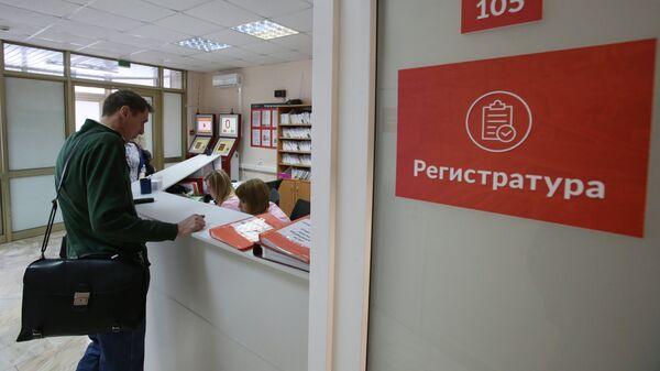Посетитель у регистрационного стола в поликлинике №180 в Москве. Архивное фото