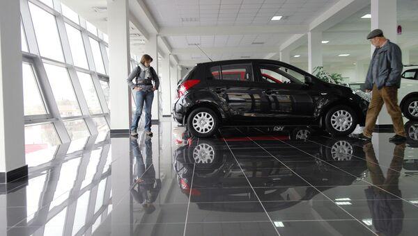 Посетители осматривают автомобиль в автосалоне