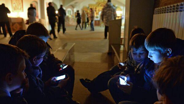 Дети играют в мобильные телефоны перед началом богослужения