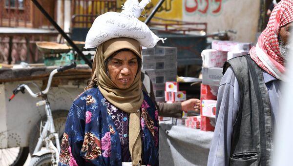 Женщина на улице сирийского города Дейр-эз-Зор