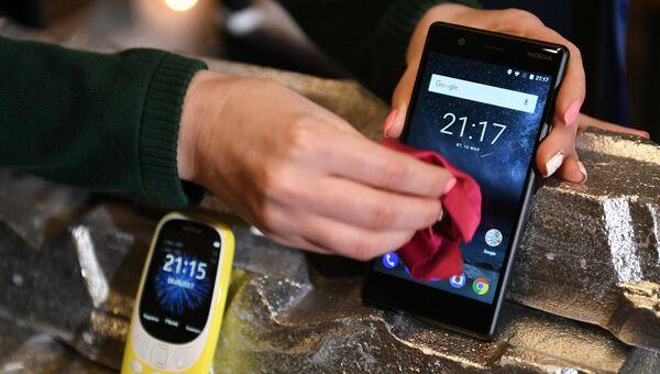 Обновленная версия классической модели мобильного телефона Nokia 3310 (слева). Архивное фото