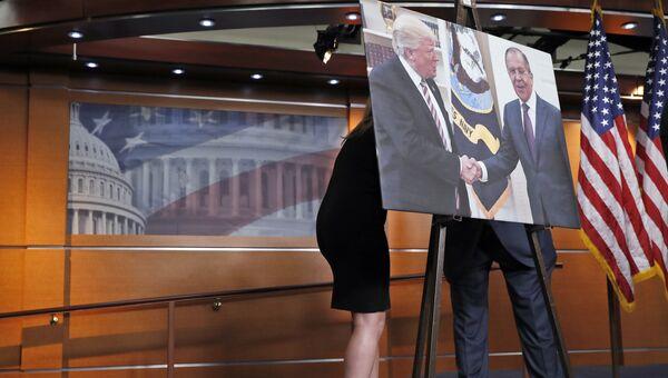 Переговоры за картиной с изображением встречи президента США Дональда Трампа и главы МИД России Сергея Лаврова в Конгрессе США