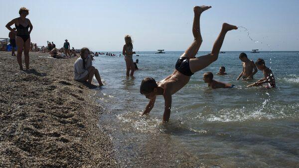 Отдыхающие на пляже Черного моря у детского оздоровительного лагеря Голубая волна в Сакском районе Крыма