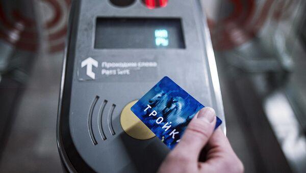Пассажир оплачивает проезд у турникета в метро. Архивное фото
