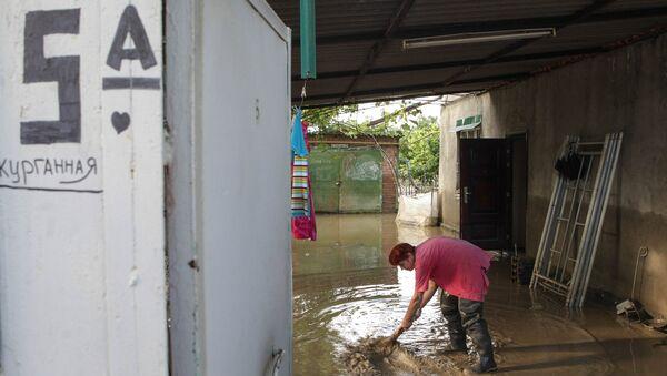 Жительница поселка Левокумка Ставропольского края во дворе дома, пострадавшего в результате паводка