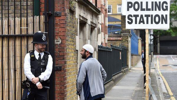 Полицейский возле избирательного участка в Тауэр-Хамлетс, Великобритания. 8 июня 2017