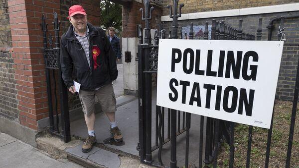 Сторонник Лейбористской партии выходит с избирательного участка в Лондоне