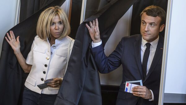 Президент Франции Эммануэль Макрон и его жена Брижит Макрон покидают избирательный участок. 11 июня 2017