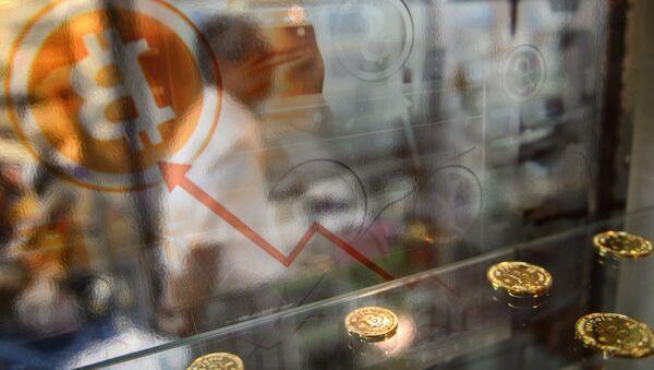 Мужчина проходит мимо витрины биткоинов. Архивное фото