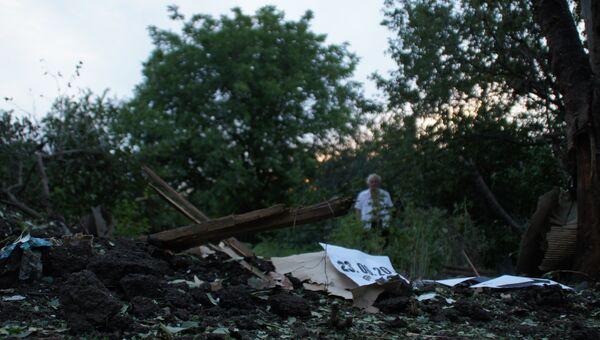 Местный житель стоит у воронки от снаряда во дворе соседского дома в Кировске, ЛНР. 23 июня 2017