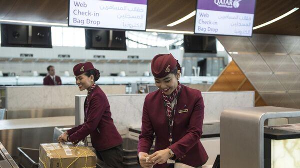 Сотрудницы авиакомпании Qatar Airways оформляют багаж пассажиров в Международном аэропорте Хамад в Дохе