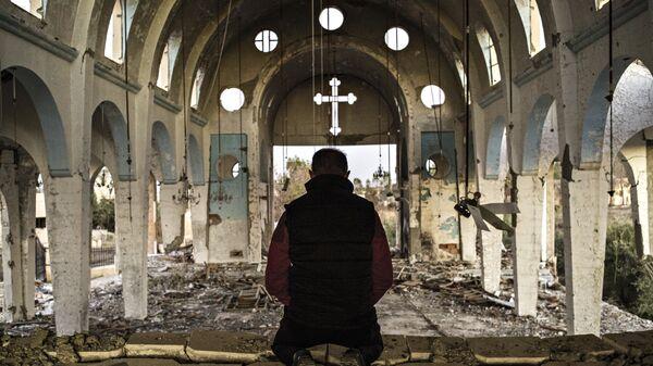 Житель одной из деревень провинции Эль-Хасаке молится в храме Святого Георгия, разрушенного боевиками ИГ.  Сирия, 08.12.2015