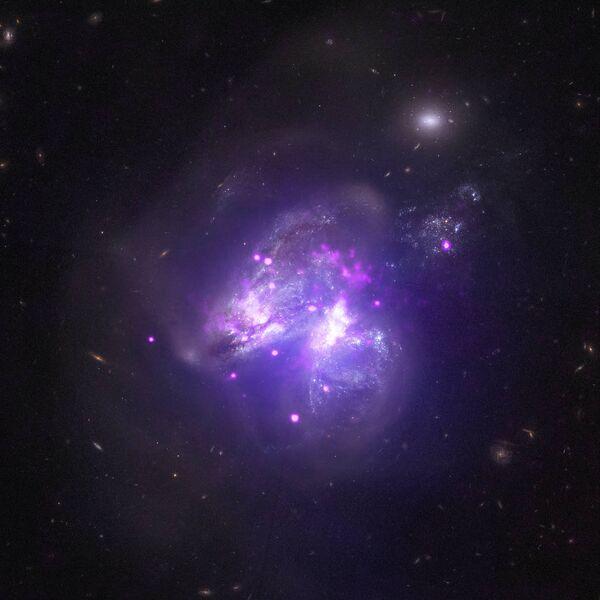 Сливающиеся галактики Arp 299 снятые телескопом Чандра