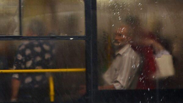 Пассажиры в автобусе во время дождя в Москве