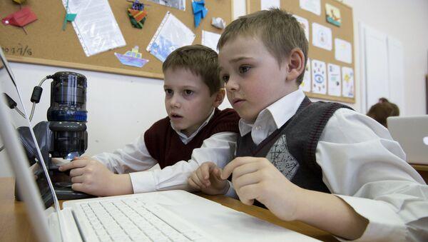 Ученики средней школы изучают предмет с помощью электронного учебника. Архив