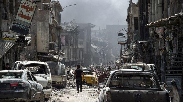 Мужчина идет вдоль сгоревших автомобилей в Мосуле