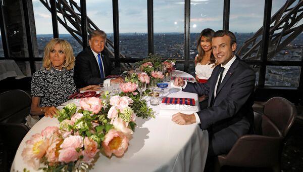 Президент США Дональд Трамп с супругой Меланьей и президент Франции Эммануэль Макрон с супругой Брижит Макрон во время ужина на Эйфелевой башне в Париже. 13 июля 2017
